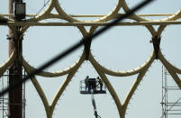In this Oct. 8, 2019 photo, laborers work on a crane by the Al Wasl Dome at the under construction site of the Expo 2020 in Dubai, United Arab Emirates. (AP Photo/Kamran Jebreili)