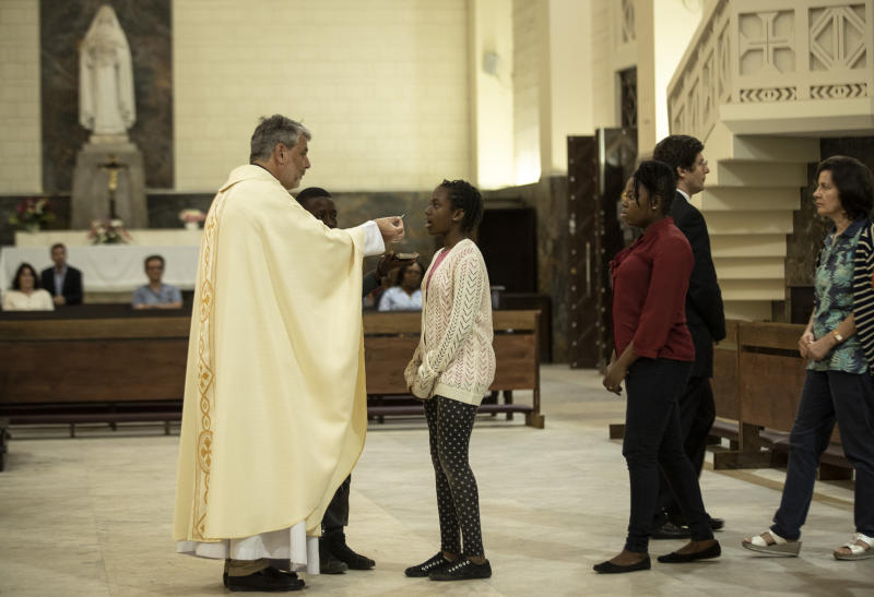 Father Giorgio gives communion during an early evening mass at the cathedral, which Pope Francis will visit later this week, in the capital Maputo, Mozambique Tuesday, Sept. 3, 2019. Pope Francis heads this week to the southern African nations of Mozambique, Madagascar and Mauritius, visiting some of the world's poorest countries in a region hard hit by some of his biggest concerns: conflict, corruption and climate change. (AP Photo/Ben Curtis)