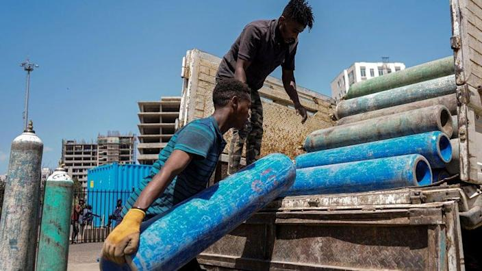 Staff members loads empty oxygen cylinders on a truck to refill at the makeshift hospital installed inside Millenium Hall, one of the country's largest event center in Addis Ababa, Ethiopia, on March 19, 2021.