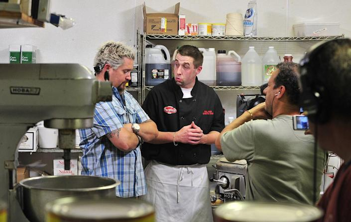 """<p>When Guy and the <em>Diners, Drive-Ins and Dives </em>team arrive on the scene, it's a smaller group than you might expect from a hit series. The show operates with <a href=""""https://people.com/food/guy-fieri-secrets-from-set-triple-d/"""" rel=""""nofollow noopener"""" target=""""_blank"""" data-ylk=""""slk:two 10-person crews"""" class=""""link rapid-noclick-resp"""">two 10-person crews</a> and often films at multiple locations at a time.</p>"""