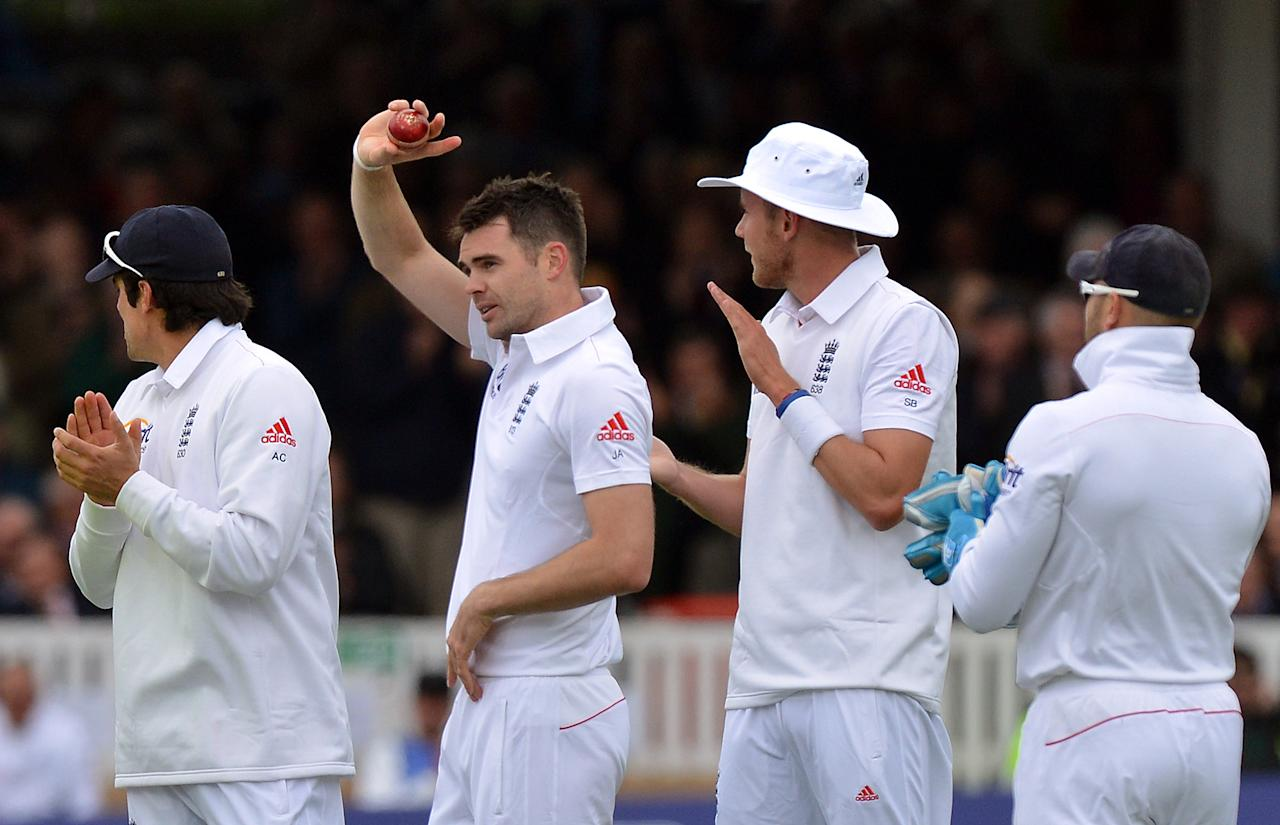 England's James Anderson holds the ball after taking his 300th test wicket, that of New Zealand's Peter Fulton, caught by Graeme Swann for 2 during the first test at Lord's Cricket Ground, London.