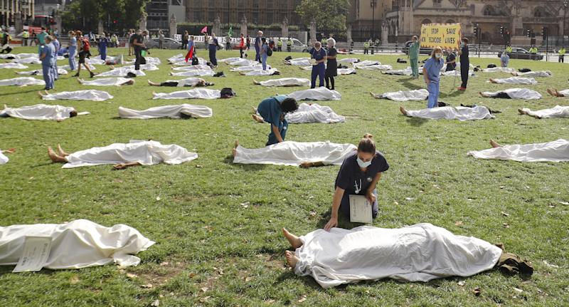 Pictured are dozens of people under white sheets on the lawn at Parliament Square.