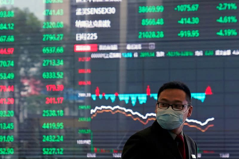 FILE PHOTO: A man wearing a protective mask is seen inside the Shanghai Stock Exchange building, as the country is hit by a new coronavirus outbreak, at the Pudong financial district in Shanghai