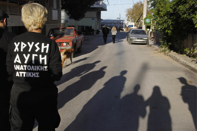 """In this Thursday, April 26, 2012 photo members of extreme far-right Golden Dawn party walk on the street as part of an election campaign in the suburban town of Artemis, 25 kilometers (15 miles) east of Athens. Reeling from a vicious financial crisis that has cost them pensions and jobs, Greeks have been turning away in droves from the mainstream politicians they feel have let them down. Firmly on the fringe of the right since it first appeared 20 years ago, Golden Dawn garnered a meager 0.23 percent in the 2009 elections. But its popularity has shot up over the past few months and support stood at about 5 percent in recent opinion polls, well above the 3 percent threshold needed to enter parliament. Writing on shirt reads: """"Golden Dawn, eastern Attica"""". (AP Photo/Petros Giannakouris)"""