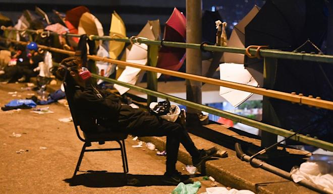 A radical protester takes a rest outside the PolyU campus. Photo: AFP