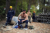 Turkish volunteers rest as they fight wildfires in Turgut village, near tourist resort of Marmaris, Mugla, Turkey, Wednesday, Aug. 4, 2021. As Turkish fire crews pressed ahead Tuesday with their weeklong battle against blazes tearing through forests and villages on the country's southern coast, President Recep Tayyip Erdogan's government faced increased criticism over its apparent poor response and inadequate preparedness for large-scale wildfires.(AP Photo/Emre Tazegul)