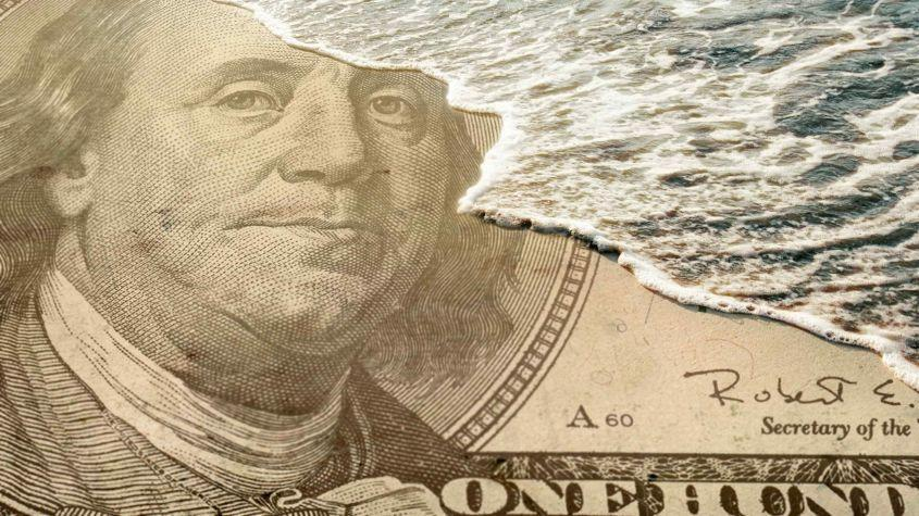 A wave washes over Ben Franklin's face on a $100 bill.