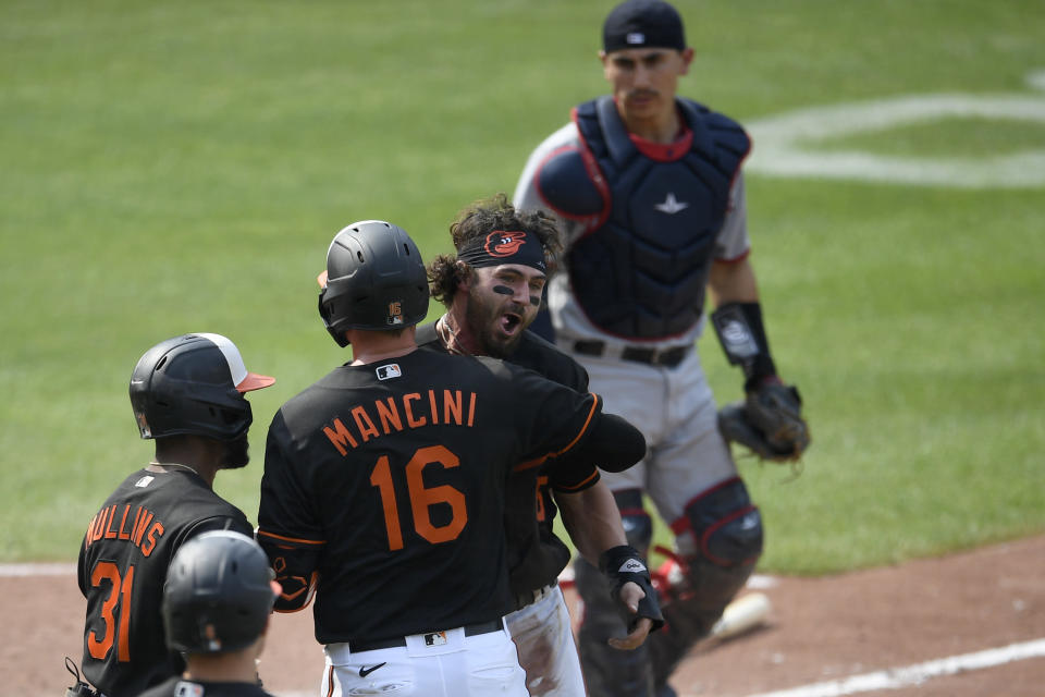 Baltimore Orioles' Ryan McKenna, third from left, reacts with Trey Mancini (16) and Cedric Mullins after he scored the game-winning run on a walk-off fielders choice by Ramon Urias during the ninth inning of a baseball game against the Washington Nationals, Sunday, July 25, 2021, in Baltimore. The play at home was challenged by the Nationals, reviewed and the call on the field was upheld. Nationals catcher Tres Barrera is at top. The Orioles won 5-4. (AP Photo/Nick Wass)