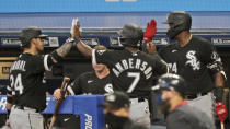 Chicago White Sox's Tim Anderson (7) is congratulated by teammates after scoring in the ninth inning in a baseball game against the Cleveland Indians, Wednesday, July 29, 2020, in Cleveland. (AP Photo/Tony Dejak)