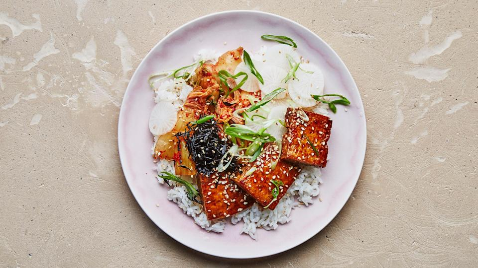 "Whenever you're cooking tofu, here's one of our no-fail techniques: Draining the tofu, then squeezing out as much water as possible (without smashing it), is the key to the crispiest cubes. <a href=""https://www.bonappetit.com/recipe/crispy-tofu-with-maple-soy-glaze?mbid=synd_yahoo_rss"" rel=""nofollow noopener"" target=""_blank"" data-ylk=""slk:See recipe."" class=""link rapid-noclick-resp"">See recipe.</a>"