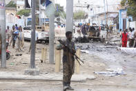 A Somali soldier secures the area after a car bomb attack at a Presidential Palace checkpoint in Mogadishu, Somalia, Saturday Sept. 25, 2021. Police said a vehicle laden with explosives rammed into cars and trucks at a checkpoint leading to the entrance of the Presidential Palace, killing at least eight people. (AP Photo/Farah Abdi Warsameh)