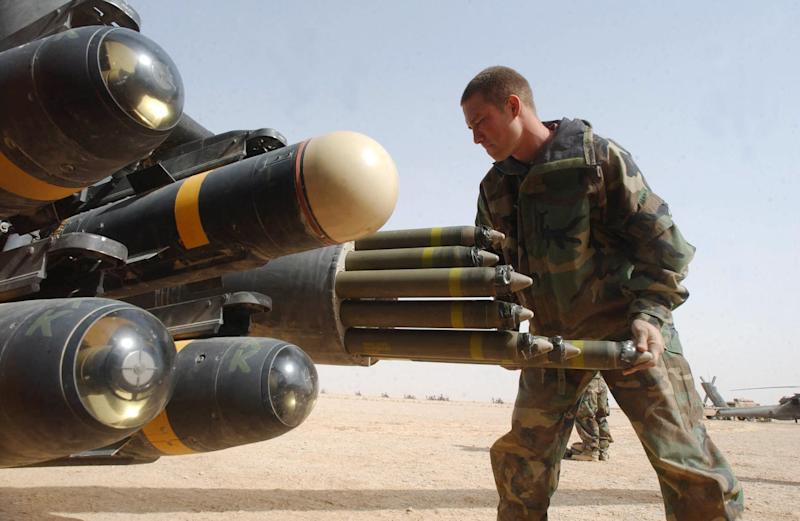 US Army armament crew specialist loads the rocket pod of an an Apache AH-64D attack helicopter also armed with Hellfire missiles in the central Iraqi desert on March 31, 2003 (AFP Photo/Romeo Gacad)