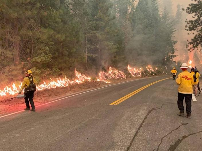 A backfire burns along Highway 168 near Lakeview Drive as firefighters attempt to burn away dry brush and starve the Creek Fire of fuel Sunday, Sept. 6, 2020.