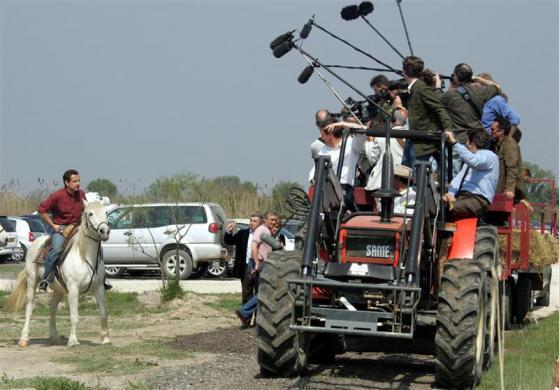 "France's UMP political party presidential candidate Nicolas Sarkozy speaks with accompanying journalists aboard a tractor as he rides ""Universe"" on a ranch in Saintes-Maries de la Mer, in Camargue region, South eastern France, April 20, 2007."