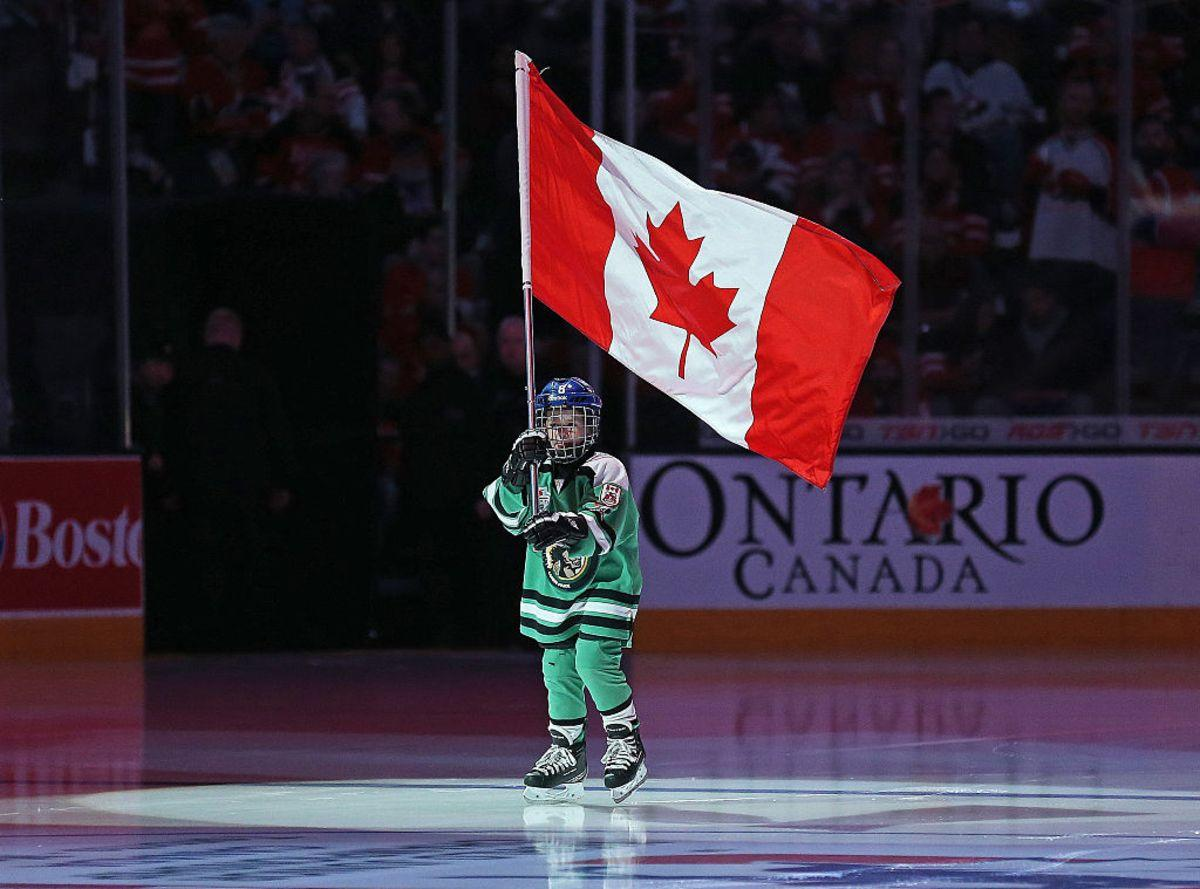TORONTO, ON - JANUARY 5: A young flag bearer carries the Canadian flag prior to play between Team Canada and Team Russia during the Gold medal game in the 2015 IIHF World Junior Hockey Championships at the Air Canada Centre on January 5, 2015 in Toronto, Ontario, Canada. Team Canada defeated Team Russia 5-4 to win the gold medal. (Photo by Claus Andersen/Getty Images)