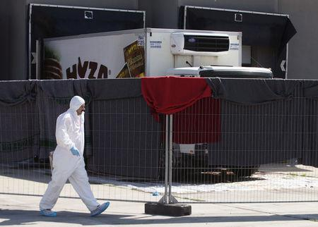 FILE PHOTO - A member of a forensic team walks in front of a truck in which more than 70 bodies were found, at a customs building with refrigeration facilities in the village of Nickelsdorf