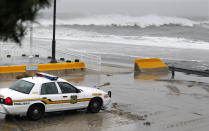A police officer watches from his patrol car as the rough Atlantic Ocean threatens streets Monday Oct. 29, 2012, in Cape May, N.J., as Hurricane Sandy continues toward landfall. Hurricane Sandy continued on its path Monday, as the storm forced the shutdown of mass transit, schools and financial markets, sending coastal residents fleeing, and threatening a dangerous mix of high winds and soaking rain. (AP Photo/Mel Evans)