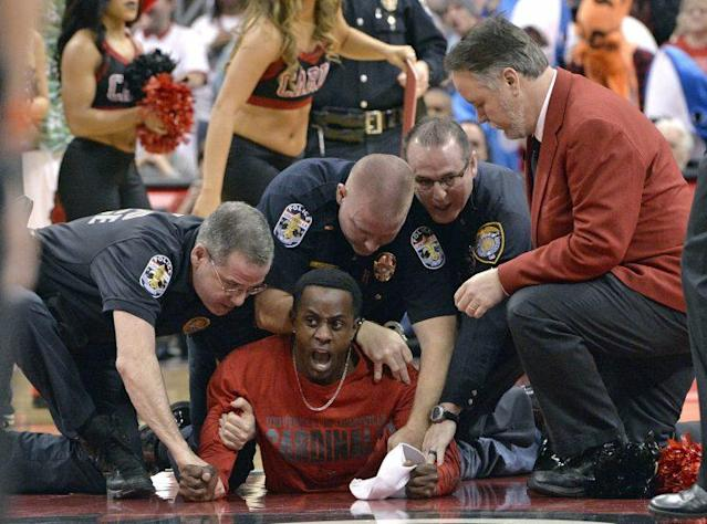 The fan entered the court from the stands during a first-half timeout, and was taken down by police. (AP)