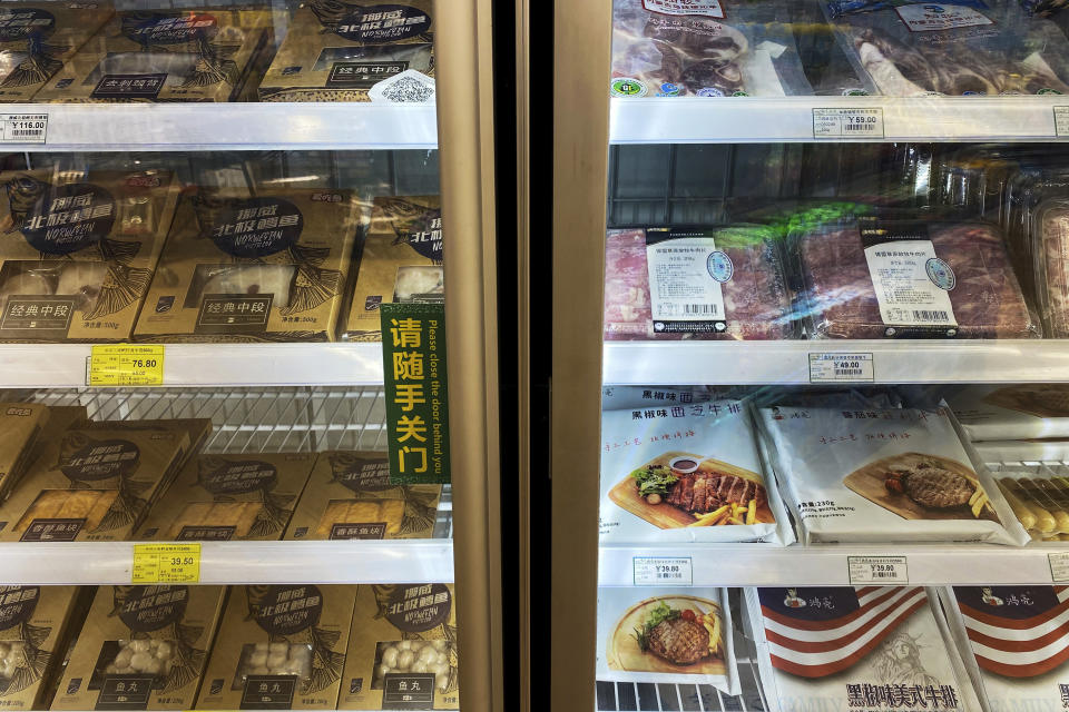 Frozen meats in imported packaging are seen inside a fridge at a supermarket in Beijing, Tuesday, Nov. 24, 2020. China has stirred controversy with claims it has detected the coronavirus on packages of imported frozen food. (AP Photo/Andy Wong)