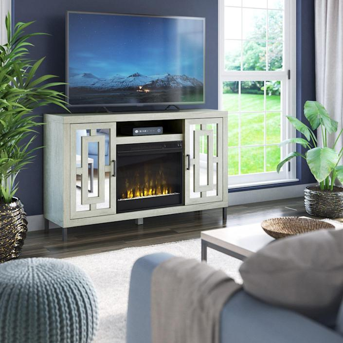 """<p><strong> Etta Avenue</strong></p><p>wayfair.com</p><p><strong>$439.99</strong></p><p><a href=""""https://go.redirectingat.com?id=74968X1596630&url=https%3A%2F%2Fwww.wayfair.com%2Ffurniture%2Fpdp%2Fetta-avenue-carter-tv-stand-for-tvs-up-to-60-with-fireplace-included-w003233655.html&sref=https%3A%2F%2Fwww.popularmechanics.com%2Fhome%2Fg37621995%2Fbest-fireplace-tv-stands%2F"""" rel=""""nofollow noopener"""" target=""""_blank"""" data-ylk=""""slk:Shop Now"""" class=""""link rapid-noclick-resp"""">Shop Now</a></p><p><strong>Key Specs</strong></p><ul><li><strong>Dimensions</strong>: 55 x 34 x 15.5 inches <br></li><li><strong>Main material</strong>: Manufactured wood</li><li><strong>Weight capacity</strong>: 150 pounds</li><li><strong>Max TV screen size: </strong>60 inches</li><li><strong>Adjustable shelves</strong>: Yes</li></ul><p>The majority of fireplace TV stands are rustic, and few lean toward glam—with the exception of this piece for sets up to 60 inches, inspired by Hollywood Regency style. It's the mirrored doors with geometric trim overlay that define its look, with adjustable shelves inside for storage. </p><p>The fireplace keeps rooms up to 400 feet toasty with 4,600 BTUs of heat, though the flame isn't adjustable and there's no remote included. But it does come with fire crystals to add sparkle as well as a faux log and ember set, plus its maximum capacity is 150 pounds.</p>"""