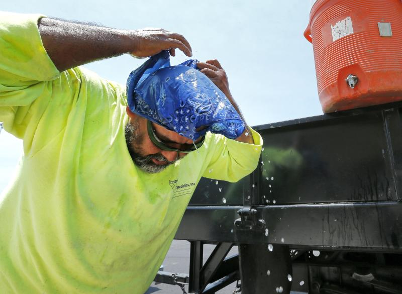 Construction worker Joel Loza puts on his bandana after soaking it in water in an effort to keep cool Thursday, June 27, 2013 in Gibert, Ariz. Excessive heat warnings will continue for much of the Desert Southwest as building high pressure triggers major warming in eastern California, Nevada, and Arizona. Dangerously hot temperatures are expected across the Arizona deserts throughout the week with a high of 118 by Friday. (AP Photo/Matt York)