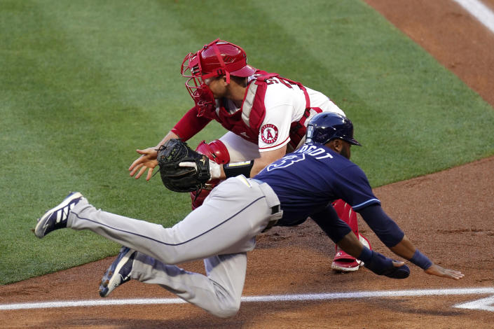 Tampa Bay Rays' Manuel Margot, below, scores after a single by Brandon Lowe and a fielding error by Los Angeles Angels second baseman David Fletcher as catcher Max Stassi takes a late throw during the first inning of a baseball game Tuesday, May 4, 2021, in Anaheim, Calif. (AP Photo/Mark J. Terrill)