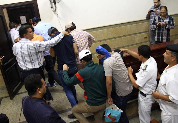 Egyptian men on trial for appearing in a video prosecutors claim was of a gay wedding on a Nile riverboat enter the courtroom in Cairo on November 1, 2014 (AFP Photo/)