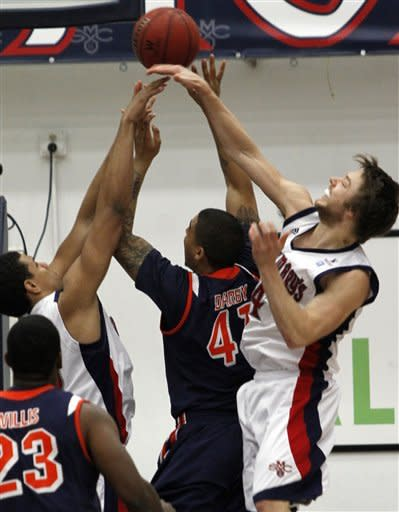 Pepperdine's Taylor Darby, center, shoots as St. Mary's Brad Waldow, left, and Matthew Dellavedova defend during the first half of an NCAA college basketball game, Thursday, Jan. 19, 2012, in Moraga, Calif. (AP Photo/George Nikitin)