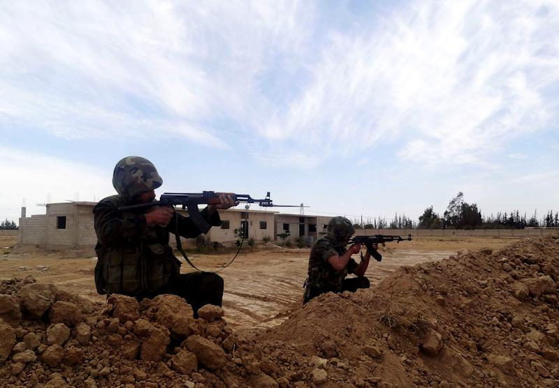 This Wednesday, April 24, 2013 photo released by the Syrian official news agency SANA, shows two Syrian Army soldiers aiming their weapons, in Otaybah town, east of Damascus, Syria. After five weeks of battle, Syrian government troops captured a strategic town near Damascus, cutting an arms route for rebels trying to topple President Bashar Assad's regime, state media and activists said Thursday. (AP Photo/SANA)