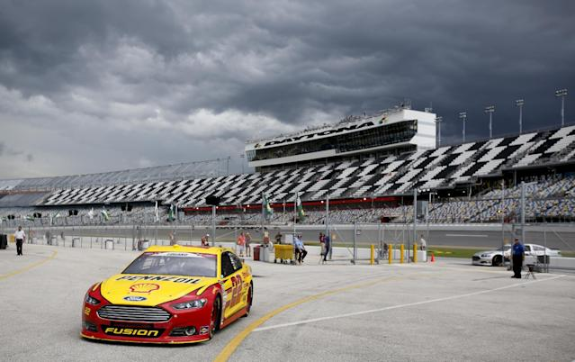 Joey Logano drives back to the garage as a storm approaches after the first NASCAR Sprint Cup practice session at Daytona International Speedway in Daytona Beach, Fla., Thursday, July 3, 2014. The second practice session was cancelled due to the bad weather. (AP Photo/Terry Renna)