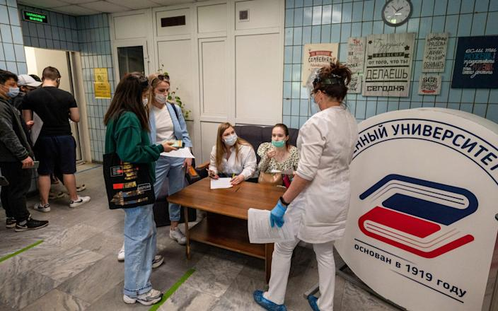 Students of the State University of Management fill in documents ahead of receiving Covid-19 vaccines in Moscow - Dmitry Serebryakov/TASS