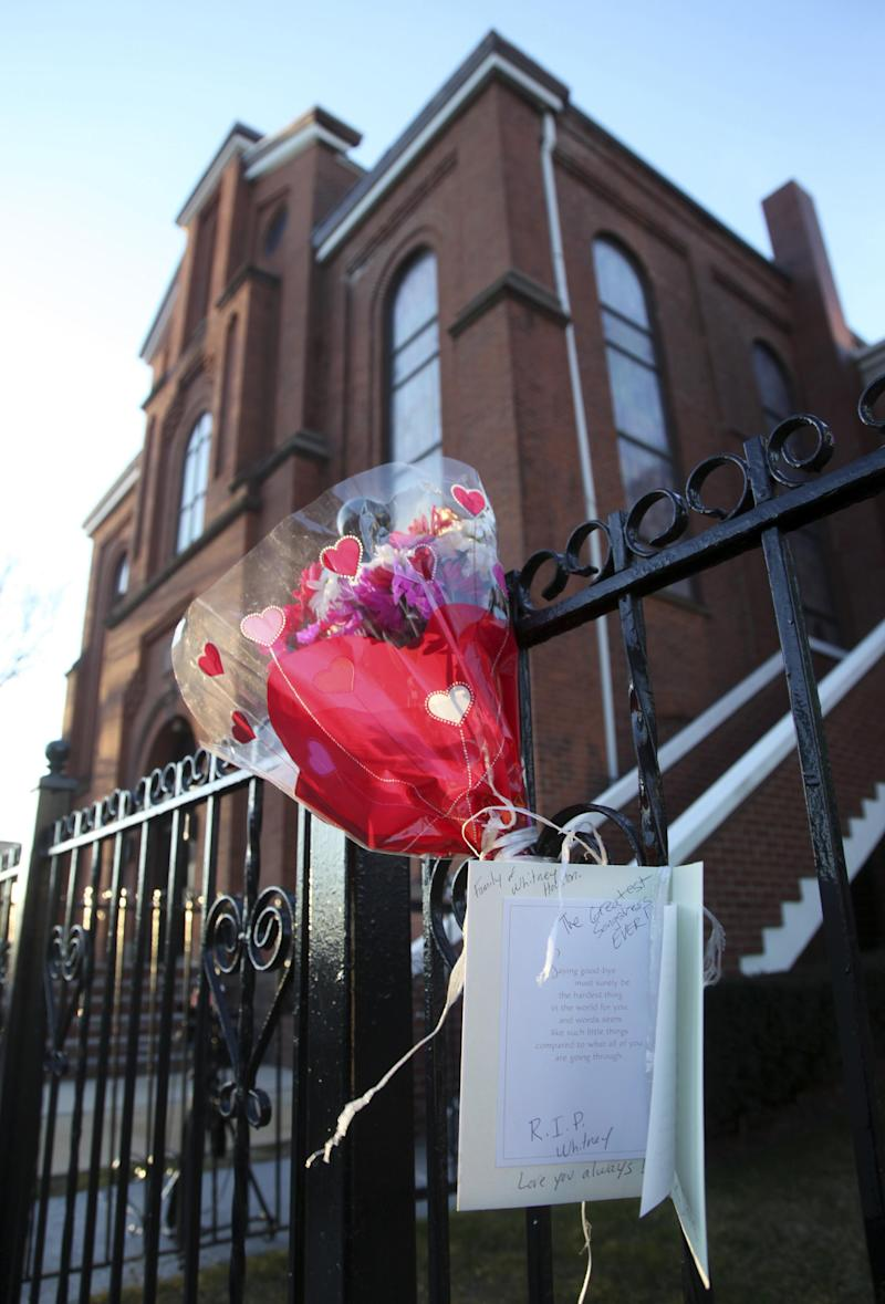 In this file photo of Sunday, Feb. 12, 2012, flowers and a card hang on a fence in front of New Hope Baptist Church in Newark, N.J. Whitney Houston's funeral will be held Saturday, Feb. 18 at the church where she sang in the choir as a girl. Houston, who ruled as pop music's queen until her majestic voice and regal image were ravaged by drug use, erratic behavior and a tumultuous marriage to singer Bobby Brown, died Saturday. She was 48.  (AP Photo/Mel Evans, file)