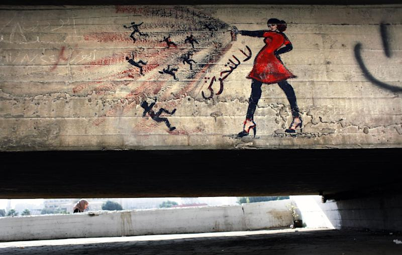 "In this Thursday, Oct. 4, 2012 file photo, an Egyptian woman walks by a mural with Arabic that reads ""no for harassing women,"" in Cairo, Egypt. Graffiti has been among the most powerful art forms and tools of Egypt's revolution and the turbulent months since, but it also has proven to be its most vulnerable and ephemeral. So a group of artists, photographers and a publisher joined hands to preserve the images. ""Wall Talk"" _ their newly released, 680-page book _ collects hundreds of photos of graffiti dating from the Jan. 25, 2011 eruption of the revolt against then-President Hosni Mubarak until today. (AP Photo/Nasser Nasser)"
