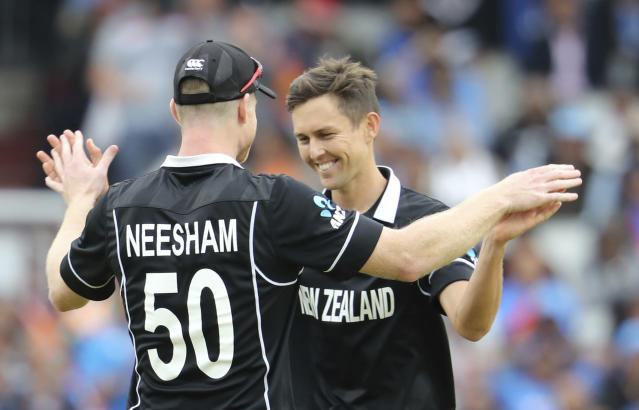 New Zealand's Trent Boult, right, celebrates with James Neesham after dismissing India's Ravindra Jadeja during the Cricket World Cup semifinal match between India and New Zealand at Old Trafford in Manchester, Wednesday, July 10, 2019. (AP Photo/Rui Vieira)