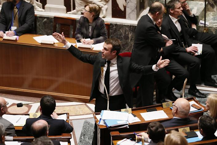 French Economy Minister Emmanuel Macron gestures during the session of questions to the government at the National Assembly in Paris on February 17, 2015 (AFP Photo/Patrick Kovarik)