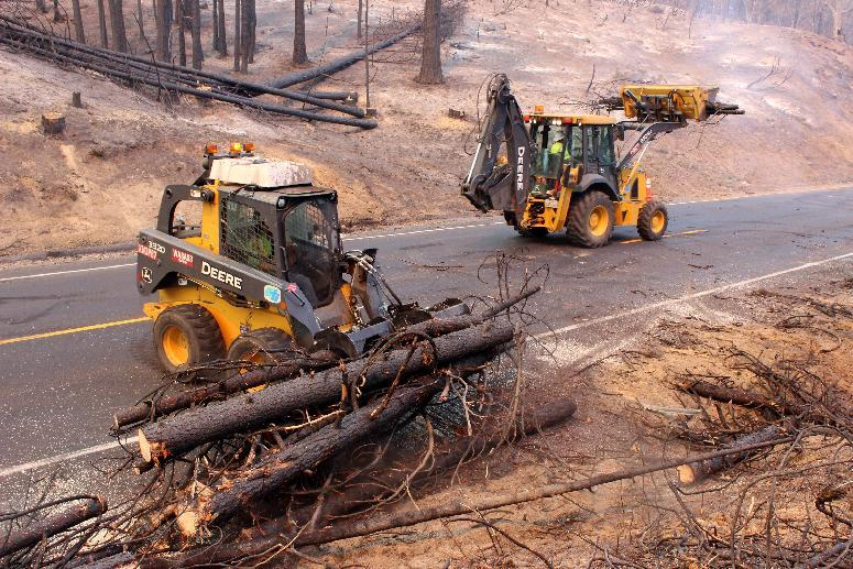 In this photo provided by the U.S. Forest Service, Crews clear California Highway 120 of debris, as crews continue to fight the Rim Fire near Yosemite National Park in California Wednesday, Sept. 4, 2013. The massive wildfire is now 80 percent contained according to a state fire spokesman. The Rim Fire's southeast flank in Yosemite National Park is expected to remain active where unburned fuels remain between containment lines and the fire. (AP Photo/U.S. Forest Service, Mike McMillan)