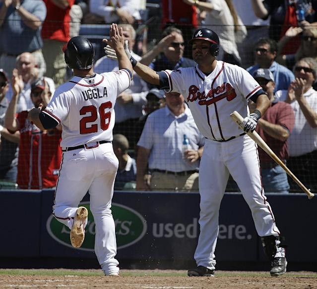 Atlanta Braves' Dan Uggla, left, high-fives teammate Gerald Laird after Uggla scored off a double by Evan Gattis in the eighth inning of a baseball game against the Miami Marlins, Wednesday, April 23, 2014, in Atlanta. The Braves won 3-1. (AP Photo/David Goldman)