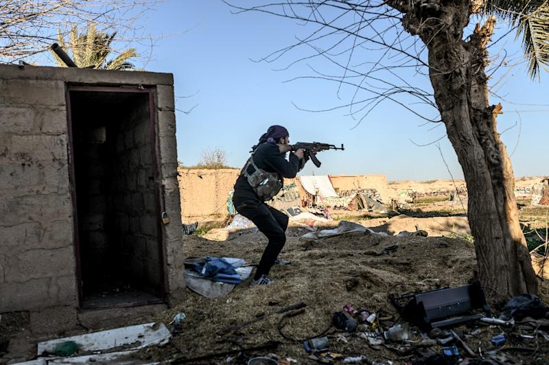 A fighter with the Syrian Democratic Forces (SDF) takes aim with his Kalashnikov assault rifle after seeing a man walking towards his position in the town of Baghouz, in the eastern Syrian province of Deir Ezzor, on March 9, 2019 (AFP Photo/BULENT KILIC)