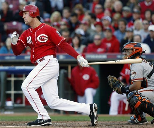 Cincinnati Reds' Ryan Ludwick (48) hits a home run against the San Francisco Giants in the third inning of Game 4 of the National League division baseball series on Wednesday, Oct. 10, 2012, in Cincinnati. Giants catcher Hector Sanchez, right, looks on. (AP Photo/David Kohl)