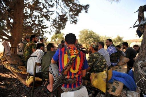 An armed Syrian rebel wearing the jersey of FC Barcelona rests with comrades near the northern city of Aleppo