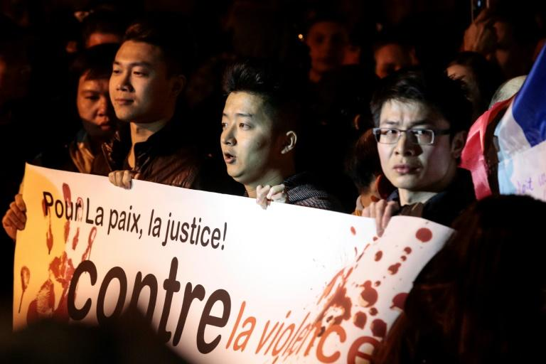 """Protestors hold a banner reading """"For peace and justice, against violence"""" at a demonstration after Paris police shoot a Chinese man, March 29, 2017"""