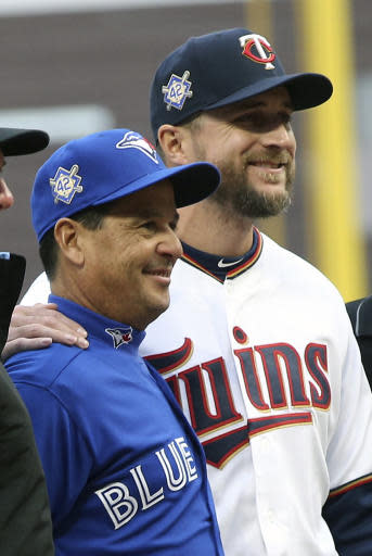 Toronto Blue Jays manager Charlie Montoya, left, and Minnesota Twins manager Rocco Baldelli pose with umpires before a baseball game Monday, April 15, 2019, in Minneapolis. The two friends were on Tampa Bay's coaching staff last season and spent several years in the Rays organization together. Both got hired as first-time managers this season. (AP Photo/Jim Mone)