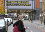 A woman wearing a face mask walks in Manchester, England, Monday, Oct. 19, 2020. Britain's government says discussions about implementing stricter restrictions in Greater Manchester must be completed Monday because the public health threat caused by rising COVID-19 infections is serious and getting worse. (Peter Byrne/PA via AP)