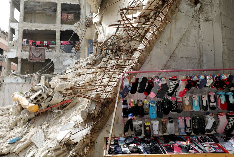Socks are displayed for sale near damaged buildings in Douma