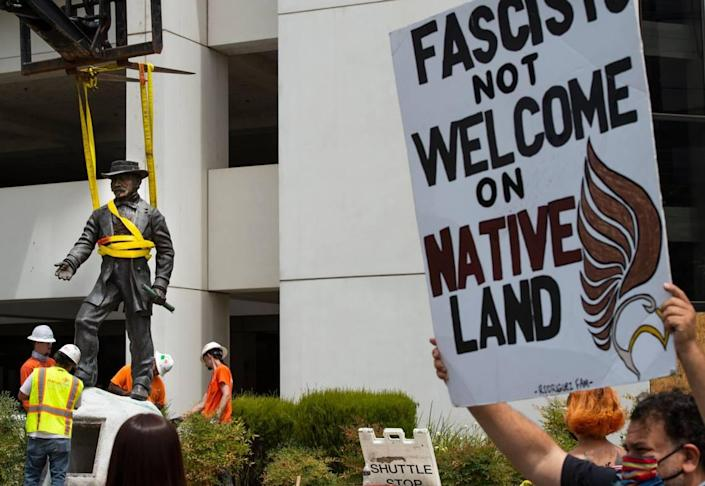 "California Native American Larry Rodriguez, right, holds up a sign while workers remove a statue of John Sutter, a Swiss settler who built the first European settlement on the site of the city of Sacramento, outside Sutter hospital in midtown on Monday, June 15, 2020. ""It's a glorious day,"" Rodriguez said. Some historical accounts describe Sutter as using Native Americans as slaves and raping Native American girls as young as age 12."