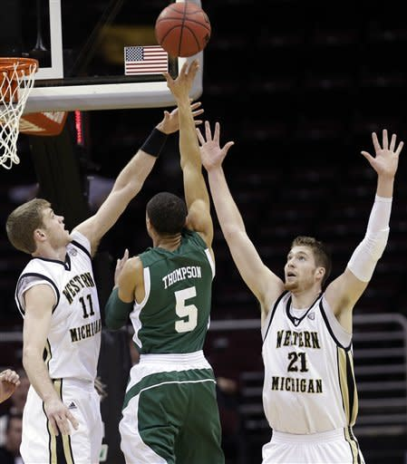Western Michigan's Nate Hutcheson (11) and Shayne Whittington (21) pressure Eastern Michigan's Derek Thompson (5) in the first half of an NCAA college basketball game at the Mid-American Conference tournament, Thursday, March 14, 2013, in Cleveland. Western Michigan won 70-55. (AP Photo/Tony Dejak)