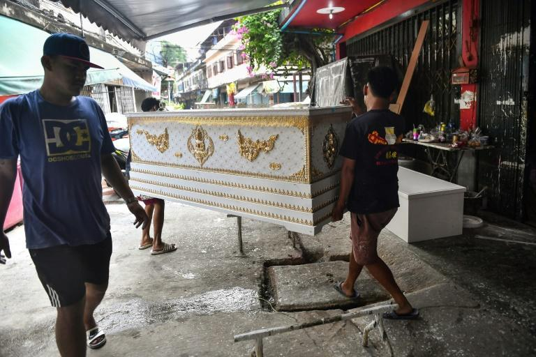 Two workshop employees carry a coffin to be recycled