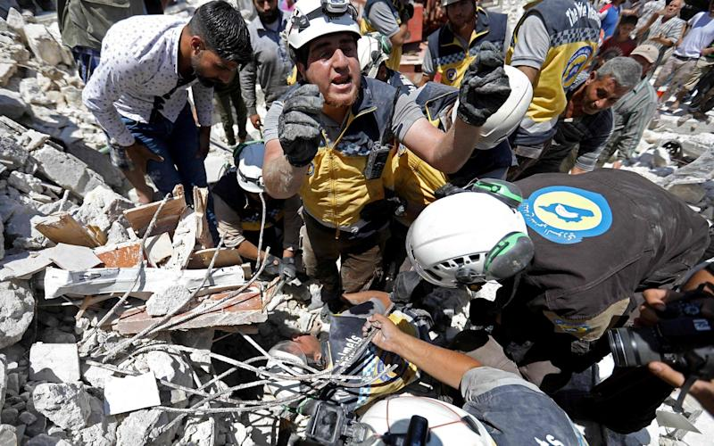 Members of the Syrian civil defence, known as the White Helmets, pull out an injured Syrian child from under the rubble following a reported Russian air strike - AFP