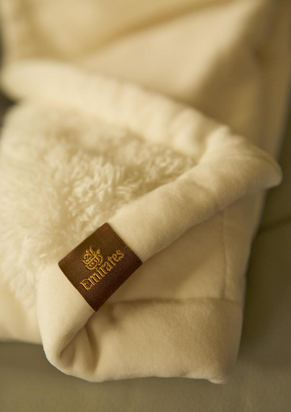 <p><span>Wave goodbye to the cheap, static blankets of economy class that literally leave your hair standing on end. Instead, snuggle down beneath a faux sheepskin blanket. Emirates offers these plush comforters to First Class passengers – and they are so popular that they now also sell them online for £48 a pop. [Photo: Emirates]</span> </p>