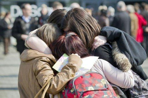 Girls comfort each other during a remembrance service in Belgium for the victims of the Swiss bus crash
